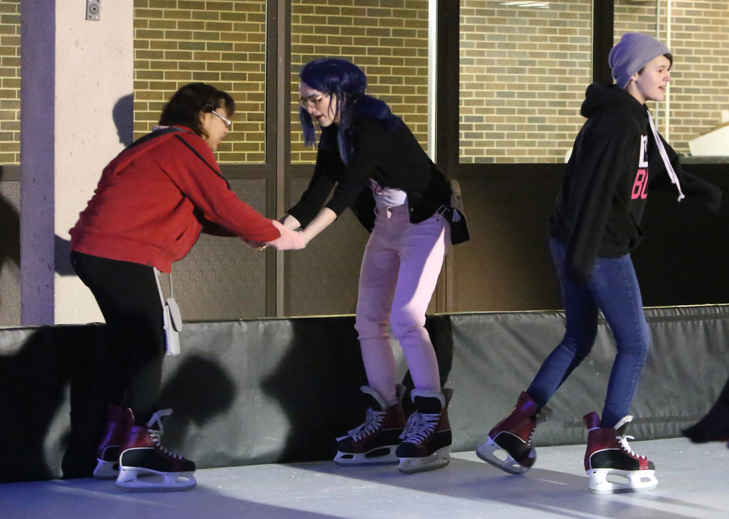 . Lowell Winterfest opening night. From left, Nichelle  DeJesus, 13, Lilah Oertel, 13, and Alysandra Cleary, 14, all of Lowell, on the artificial ice skating rink at JFK Plaza. (SUN Julia Malakie)