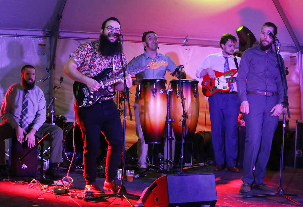 . Lowell Winterfest opening night. The Squires of Soul perform at the JFK Plaza tent. From left: Chuck Kuenzler of Dracut on cajon (box drum), Harry Borsch of Lowell on guitar and vocals, Keith Patenaude of Derry, N.H. on drums, Matt Nimeskal of Haverhill on bass, and Cam Anthony of Lowell on vocals. (SUN Julia Malakie)
