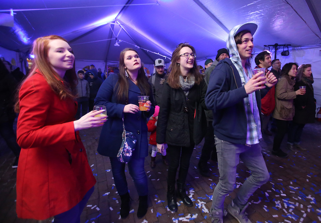 . Lowell Winterfest opening night. From left, friends Ashley Hillson, Briana McGrade, Rebecca Tourville and Keith Boisvert, all of Dracut, at the JFK Plaza music tent, where the Squires of Soul were performing. (SUN Julia Malakie)