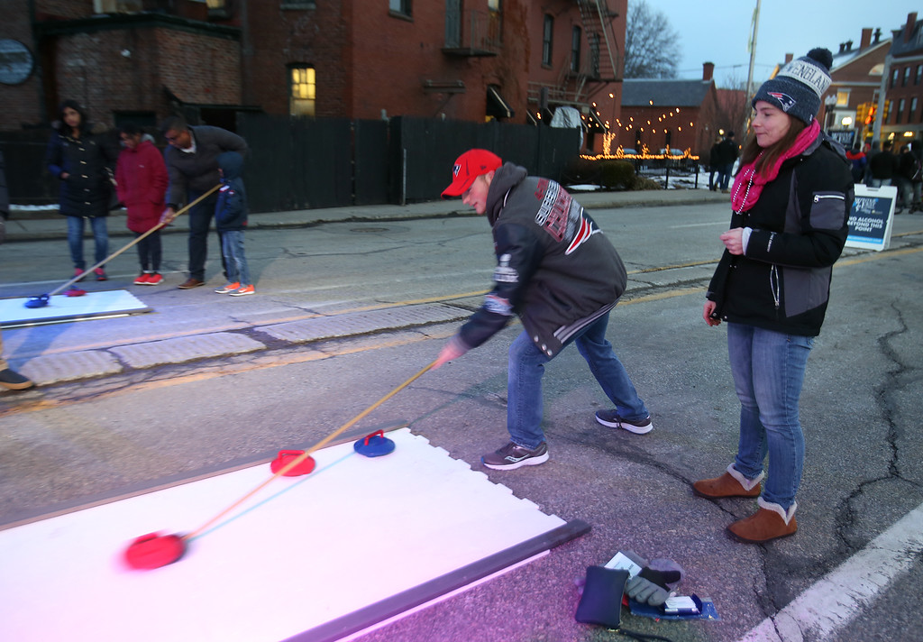 . Lowell Winterfest opening night. Meghan Richard and her son Logan, 14, of Lowell, try curling on artificial ice. (SUN Julia Malakie)