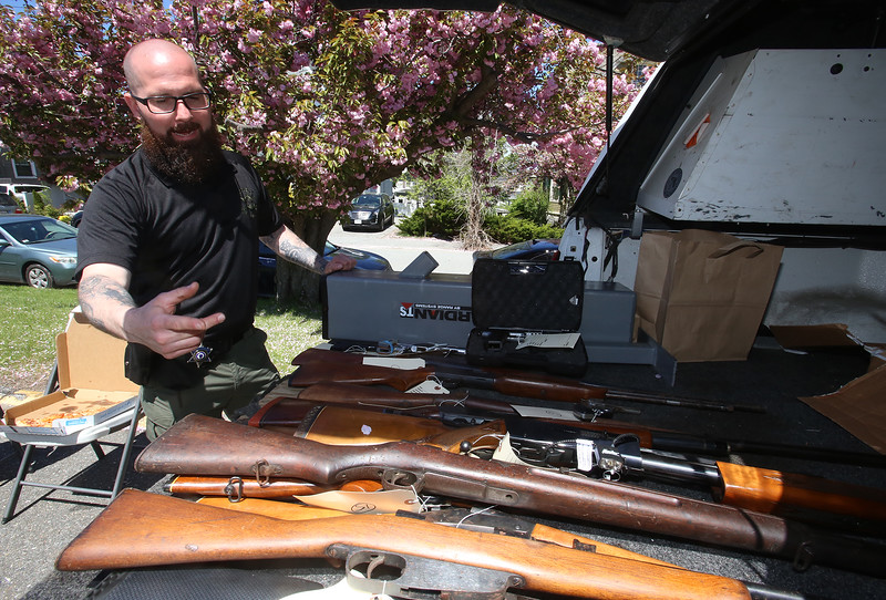 "Current and former Lowell High students, interfaith organizations, and Middlesex Sherriff's Department and Lowell Police hold 3rd annual ""Safer Homes, Safer Community: Gift Cards for Guns"" exchange he Community Christian Academy parking lot. Middlesex Sheriiff's Office Sgt. Chris Foley shows the 16 guns turned in so far, which included 11 long rifles, 1 BB gun and 4 pistols.  (SUN/Julia Malakie)"