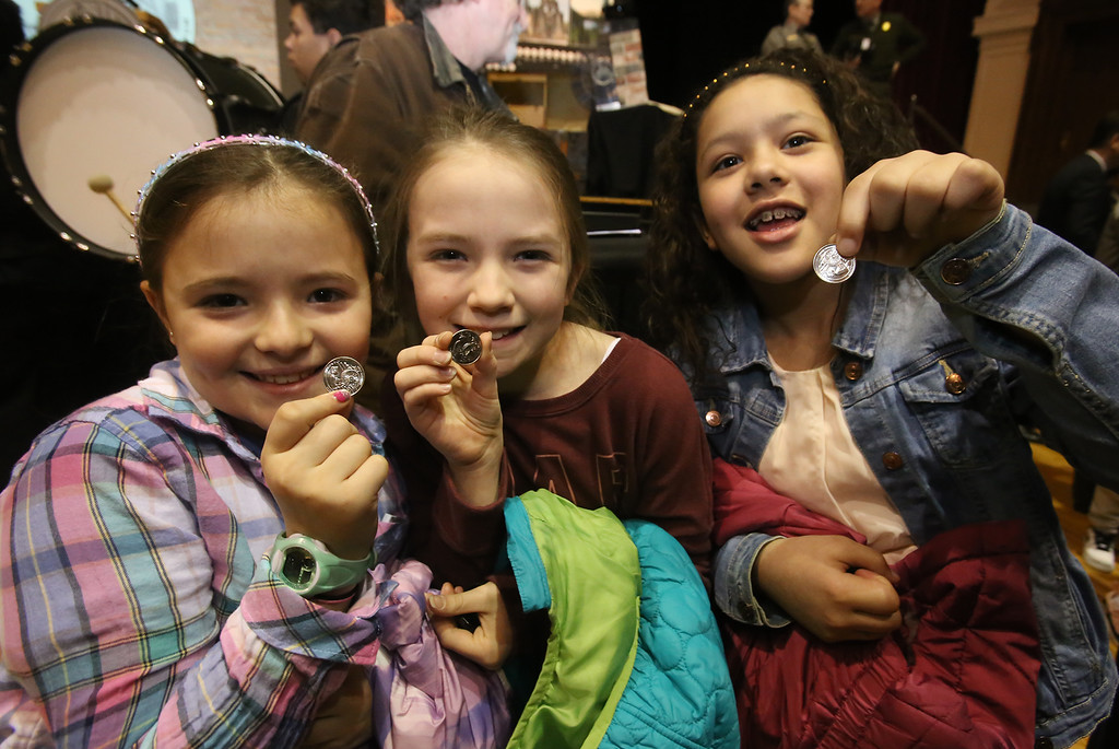 . Launch and coin exchange for the Lowell quarter, representing Massachusetts as the 46th coin in the US Mint\'s America the Beautiful Quarters Program. Reilly School 4th graders, from left, Alexia Anderson, 10, Phebe Karner, 9, and Ana Martinez, 9, with their quarters. Everyone under 18 got a free quarter.(SUN/Julia Malakie)