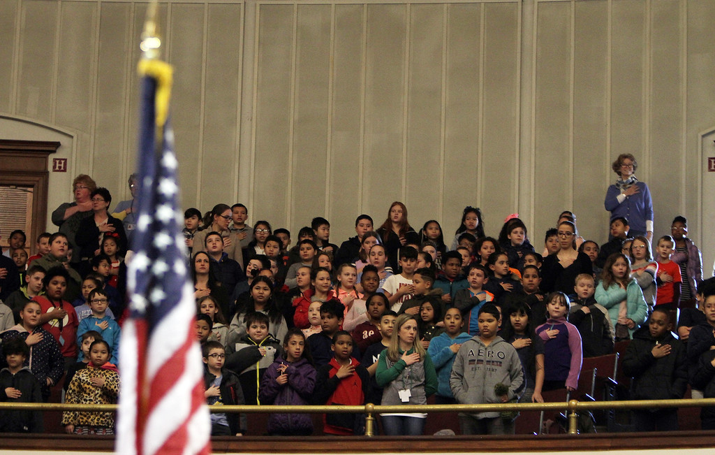 . Fourth graders in balcony stand for Pledge of Allegiance, at aunch and coin exchange forl the Lowell quarter, representing Massachusetts as the 46th coin in the US Mint\'s America the Beautiful Quarters Program. (SUN/Julia Malakie)