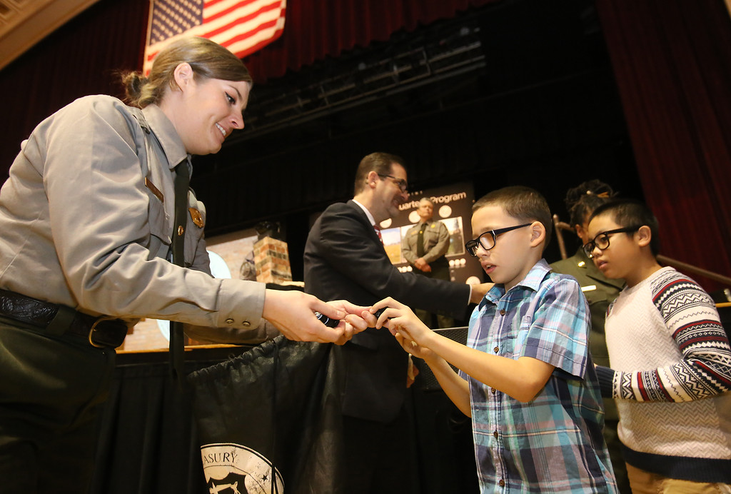 . Launch and coin exchange for the Lowell quarter, representing Massachusetts as the 46th coin in the US Mint\'s America the Beautiful Quarters Program. National Park Service park planner Christine Bruins hands out quarters to Shaughnessy School 4th graders Brendon King, 9, center, and Delonte Ath, 10. (SUN/Julia Malakie)