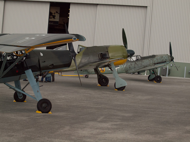 The Fieseler Fi 156 Storch, Focke-Wulf Fw-190 A-5, and Messerschmitt Bf-109E-3 Emil lined up awaiting the start of Luftwaffe Fly Day outside the Flying Heritage Collection at Paine Field in Everett, WA on August 17, 2013.