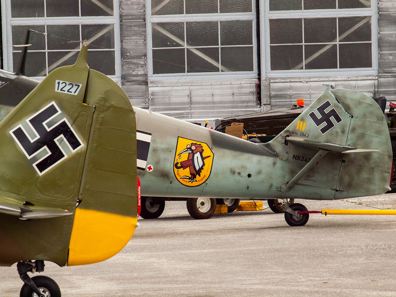 Tails of the Focke-Wulf Fw-190 A-5, and Messerschmitt Bf-109E-3 Emil awaiting the start of Luftwaffe Fly Day outside the Flying Heritage Collection at Paine Field in Everett, WA on August 17, 2013.