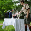 5/29/16 LUNENBURG-- Luke Marshall, 16, of Boy Scout Troop 1728, placing a rose on an empty table to remember lost veterans during Sundays Memorial Day ceremony at the Eagle House Senior Center in Lunenburg.  Sentinel & Enterprise photo/Jeff Porter