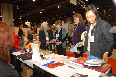 EB2007:  (L-to-R) Drs. Ida Chow, Judy Venuti and Kathy Svoboda and unidentified participant review information available at the AAA Exhibit Booth.