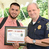 Fitchburg Police Sergeant Glenn Fossa presents Kenneth Diaz with a certificate during the recognition luncheon to honor sponsors, employers, and participants of MOC's Jobs4Youth summer program on Thursday afternoon. SENTINEL & ENTERPRISE / Ashley Green