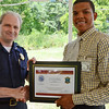 Fitchburg Police Sergeant Glenn Fossa presents Diosmar Reynoso with a certificate during the recognition luncheon to honor sponsors, employers, and participants of MOC's Jobs4Youth summer program on Thursday afternoon. SENTINEL & ENTERPRISE / Ashley Green