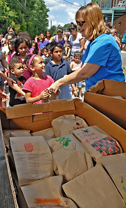 06-07-12  --must summer lunch 10--  Paula Rigsby, Seasonal Programs Coordinator and Summer Lunch Coordinator for MUST Ministries, hands out sack lunches to children at the second stop on her route in Marietta on Thursday morning.  Volunteers are welcome to decorate the brown paper bags which can serve as an ice breaker for some of the children in the communities.  STAFF/LAURA MOON.