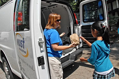 06-07-12  --must summer lunch 05--  Paula Rigsby, Seasonal Programs Coordinator and Summer Lunch Coordinator for MUST Ministries, hands out sack lunches for children that are present along her route in Smyrna and Marietta on Thursday morning.  STAFF/LAURA MOON.