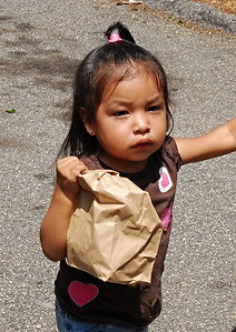 06-07-12  --must summer lunch 12--  Alison Delrio, 2, walks away with her free lunch on Thursday morning.  After three stops on Route 1, Paula Rigsby delivered approximately 150 sack lunches to children in Smyrna and Marietta on Thursday morning.  STAFF/LAURA MOON.