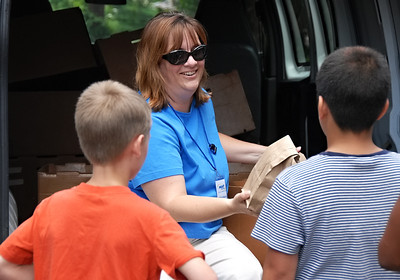 06-07-12  --must summer lunch 13--  Paula Rigsby hands out sack lunches to children at the third stop on her route in Marietta on Thursday morning.  Rigsby began volunteering as a summer lunch driver one day a week 11 years ago and is now the Seasonal Programs Coordinator and Summer Lunch Coordinator for MUST Ministries.  STAFF/LAURA MOON.
