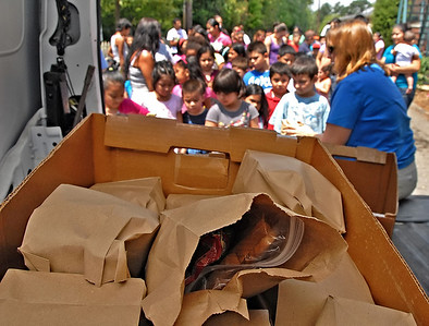 06-07-12  --must summer lunch 11--  Paula Rigsby, Seasonal Programs Coordinator and Summer Lunch Coordinator for MUST Ministries, hands out sack lunches to children at the second stop on her route in Marietta on Thursday morning.  Each lunch contains a sandwich, salty snack, sweet snack and a drink.  STAFF/LAURA MOON.