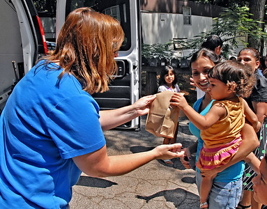 06-07-12  --must summer lunch 06--  Paula Rigsby, Seasonal Programs Coordinator and Summer Lunch Coordinator for MUST Ministries, hands a sack lunch to Maria Hernandez' daughter Darlah Blanco in Smyrna on Thursday morning.  STAFF/LAURA MOON.