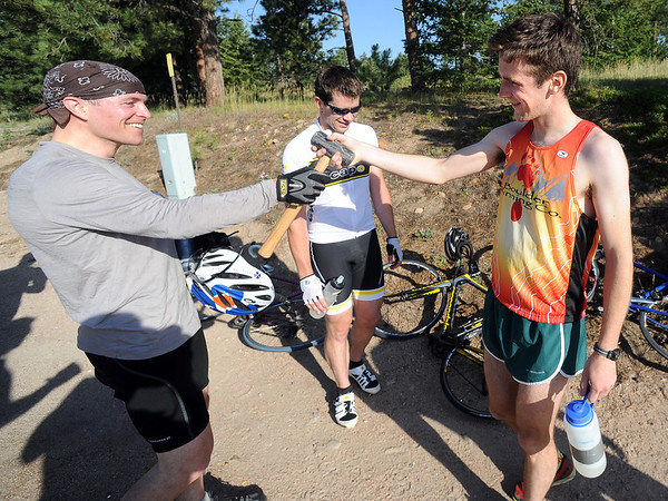 "Jason Lawrence, left, accepts the John Henry Hammer from runner, Dan Gorman, after winning the 5-mile race up Flagstaff Mountain.<br /> The ""John Henry Challenge"", was held on Friday, with a man vs machine race up Flagstaff Mountain.  The race is named in honor of John Henry the ""steel driving man"" who worked by hand and hard labor and nearly beat the steam hammer to lay railroad tracks.  Eight cyclists from Boulder Wind Power  challenged one of their colleague Dan Gorman, a nationally ranked runner who thought he can make it up to the summit of Flagstaff before any of the cyclists. <br /> For more photos and a video of the race, go to  <a href=""http://www.dailycamera.com"">http://www.dailycamera.com</a><br /> Cliff Grassmick / June 14, 2012"
