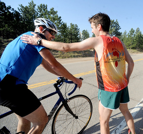 "Dan Gorman, right,  congratulates Cisco Oyague, after the 5-mile race up Flagstaff Mountain.<br /> The ""John Henry Challenge"", was held on Friday, with a man vs machine race up Flagstaff Mountain.  The race is named in honor of John Henry the ""steel driving man"" who worked by hand and hard labor and nearly beat the steam hammer to lay railroad tracks.  Eight cyclists from Boulder Wind Power  challenged one of their colleague Dan Gorman, a nationally ranked runner who thought he can make it up to the summit of Flagstaff before any of the cyclists. <br /> For more photos and a video of the race, go to  <a href=""http://www.dailycamera.com"">http://www.dailycamera.com</a><br /> Cliff Grassmick / June 14, 2012"