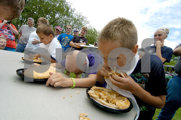 -Messenger photo by Hans Madsen<br /> <br /> Carson Widlund, 8, of  Manson works on putting a whole pie away Saturday afternoon during the Manson Lions Club pie eating contest at Manson Crater Days. At left, Reyd Wood, 11, also of Manson, takes a short break to regroup.