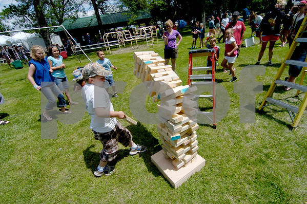 -Messenger photo by Hans Madsen<br /> <br /> Israel Chalstrom, 8, of Manson, gets out of the way as the last log he removed caused the giant game of Jenga he was playing Saturday at the Manson Crater Days to topple over.