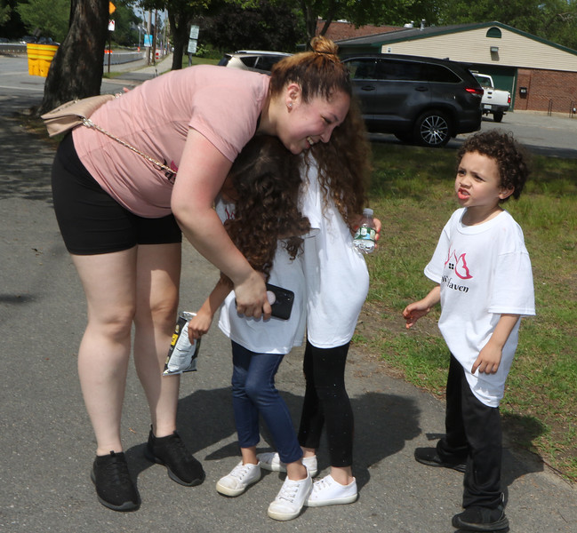 Shout Walk-a-thon against domestic violence, along Pawtucket Boulevard ending at Sampas Pavilion. Yashira Hernandez of Danvers, who hopes to open a domestic violence safe house, is greeted by daughters Alayasia, 6, and Isabella, 7, and son Carter, 5, as she arrives at Sampas Pavilion.  SUN/Julia Malakie