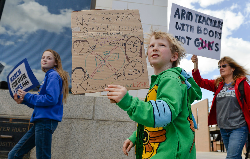 Justin Sheely | The Sheridan Press<br /> Seven-year-old Riley Cody marches with his sign during The March for Our Lives demonstration on Main Street in Sheridan Saturday, March 24, 2018. Sheridan area students and community members participated in the march in solidarity with the rally in Washington, D.C.