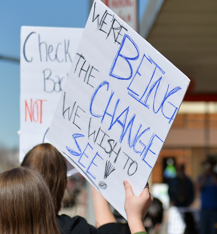 Justin Sheely | The Sheridan Press<br /> Marches walk along the sidewalk during The March for Our Lives demonstration on Main Street in Sheridan Saturday, March 24, 2018. Sheridan area students and community members participated in the march in solidarity with the rally in Washington, D.C.