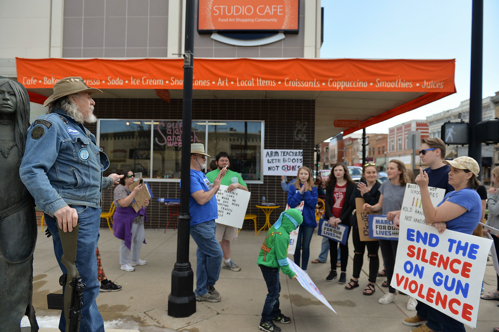 Justin Sheely | The Sheridan Press<br /> Sheridan resident David Kuzara, left, argues with the marchers while holding a BB gun styled as an M1 rifle during The March for Our Lives demonstration on Main Street in Sheridan Saturday, March 24, 2018. Kuzara argued with the marchers on gun control legislation.