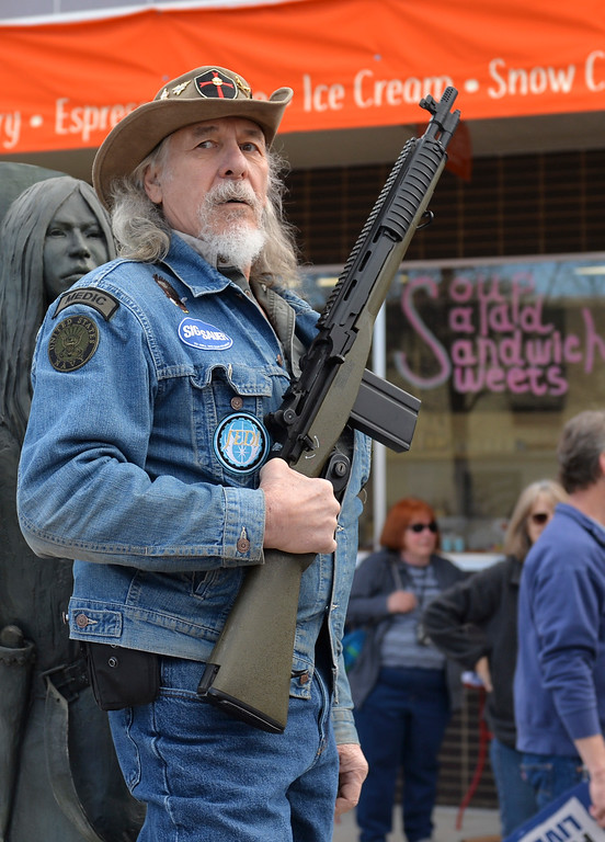 Justin Sheely | The Sheridan Press<br /> Sheridan resident David Kuzara holds a BB gun styled as an M1 rifle during The March for Our Lives demonstration on Main Street in Sheridan Saturday, March 24, 2018. Kuzara argued with the marchers on gun control legislation.