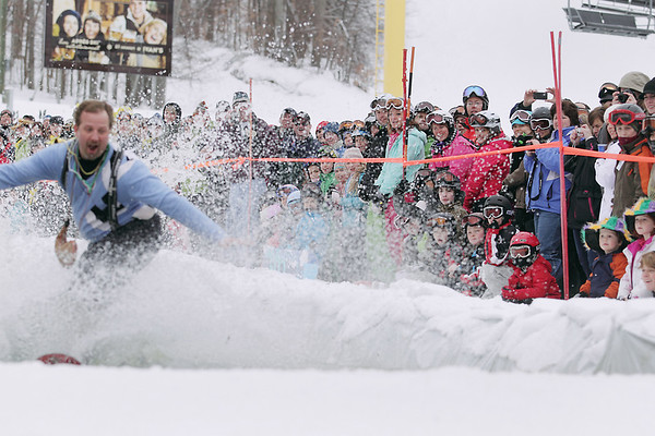 Record-Eagle/Keith King<br /> Spectators watch as Craig Gossett, of Royal Oak, rides his snowboard across a pool of water Saturday, March 5, 2011 during Mardi Gras & Slush Cup Weekend at Shanty Creek Ski Resort.