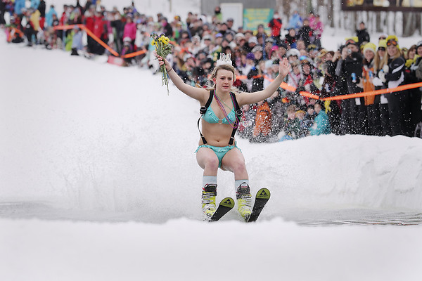 Record-Eagle/Keith King<br /> Holding flowers in the air, Sarah Hoppie, of Bloomfield Hills, skis across a pool of water Saturday, March 5, 2011 during Mardi Gras & Slush Cup Weekend at Shanty Creek Ski Resort. Hoppie successfully skied across the pool of water.