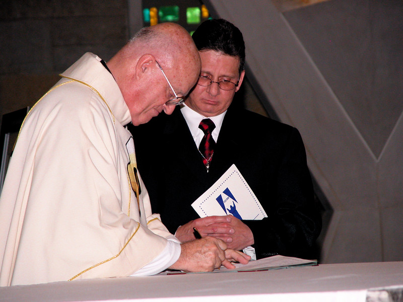 Fr. MacDonald signs Frater Mark's profession papers.