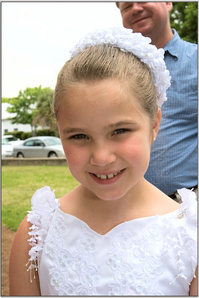Pretty girl in her first communion dress, Proud papa watching her get her picture taken.