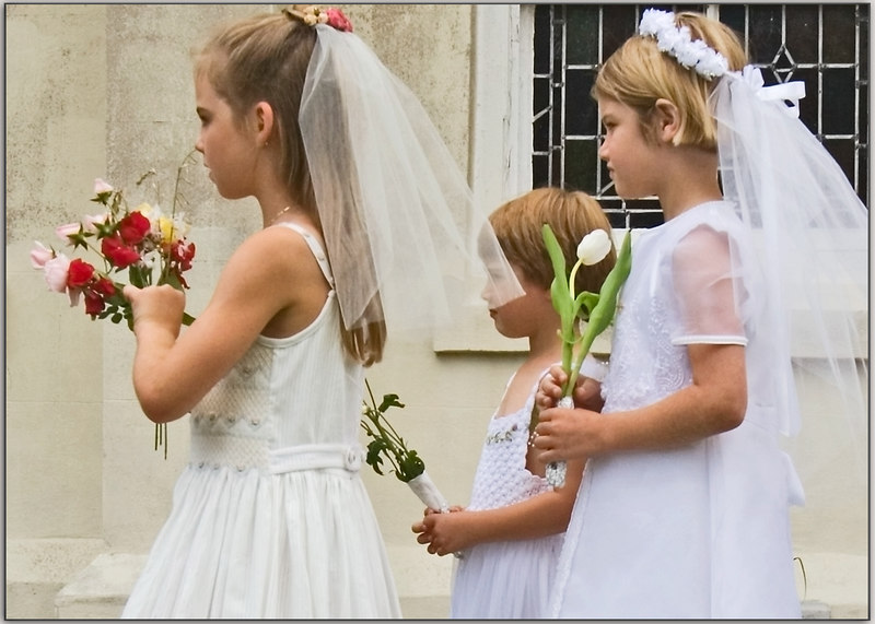 Children in their first communion dresses carry flowers as the procession begins.