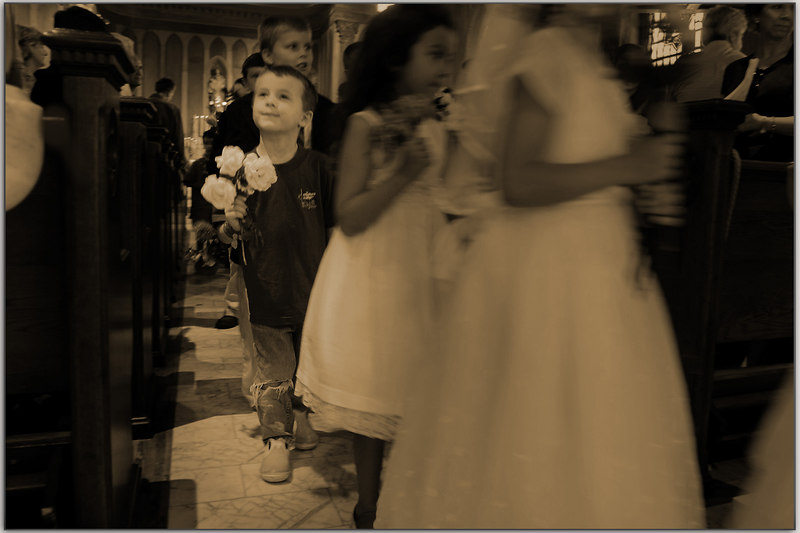 The photographer did not check her flash connection and thereby did not get any good pictures inside the church.<br /> However this little boy just begged to be shown.  His torn jeans, along with an angelic expression while holding flowers, it is a heart tugger.