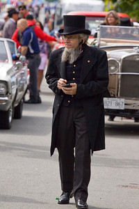 Man in period attire talking on his handsfree cellphone. May Day celebrations in Port Coquitlam 2013