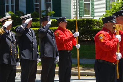 Pre-parade Salute - Lined up before the parade route, these firefighters and police salute the flag.
