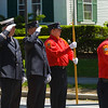 Pre-parade Salute -<br /> Lined up before the parade route, these firefighters and police salute the flag.