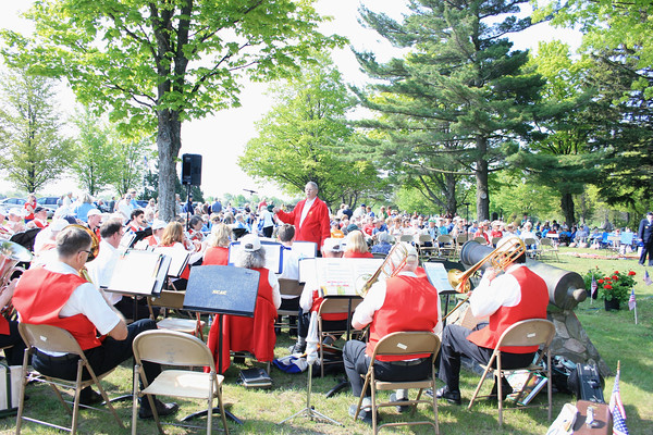 Record-Eagle/Loraine Anderson<br /> Don Wilcox, retired University of West Virginia music director, leads the Northport Community Band as hundreds of people gather to observe Memorial Day at the Leelanau Township Cemetery in Northport.