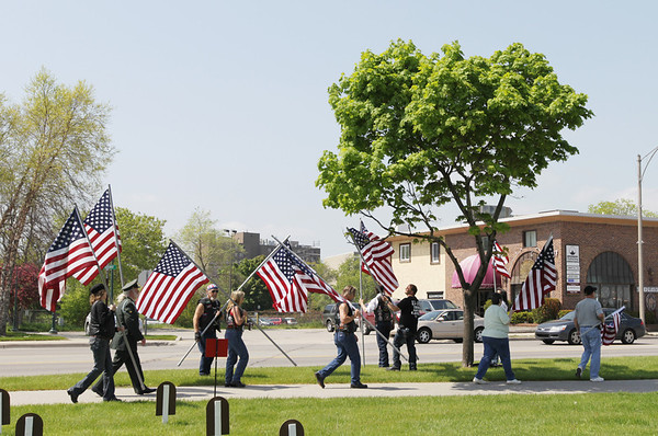 Record-Eagle/Keith King<br /> Flags are carried along Grandview Parkway to prepare Monday, May 30, 2011 for the Patriots Flag Line.