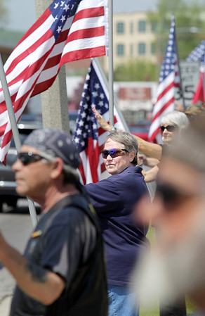 """Record-Eagle/Keith King<br /> Peg Waterman, of Kalkaska, holds a flag along Grandview Parkway as part of the Patriots Flag Line Monday, May 30, 2011 in Traverse City. """"I love my United States,"""" Waterman said."""