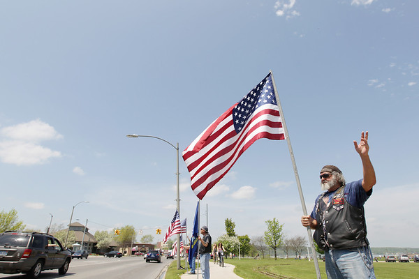 Record-Eagle/Keith King<br /> Lee White, of Rapid City, also a member of the United States Air Force from 1956 until 1960, waves to passing motorists while he stands as part of the Patriots Flag Line Monday, May 30, 2011 along Grandview Parkway in Traverse City.