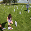 Record-Eagle/Keith King<br /> Savannah Lentz, left, of Manton, her son, Dante Kinga, six months old, and her sister, Lenzy Blakeslee, of Manton, observe a memorial for their brother (Kinga's Uncle), Dillon Foxx, Monday, May 30, 2011 at the Open Space. Markers were placed in the ground at the Open Space by Veterans for Peace Chapter 50 for Michigan servicemen and servicewomen killed in Iraq and Afghanistan.