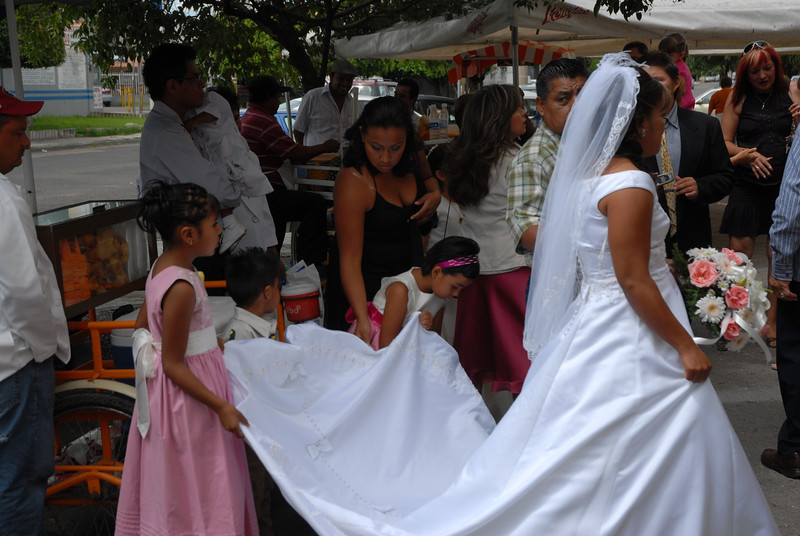 The bride with her son and daughter  and niece holding her train preparing to enter the church.