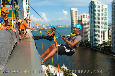 "In an adrenaline-rushing demonstration of their commitment to improve the lives of Miami children and families, the first ""Over The Edge"" rappellers, Aubrina Mumford and Les Bradley, prepare to go 19 stories down the JW Marriot Marquis on Sept. 5, 2013."