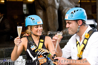 "Univision TV personalities, Gloria Ordaz (News Anchor) and Enrique Santos (host of Univision's ""Enrique Santos Show"") celebrate their ""Over The Edge"" landing over a class of champagne on Sept. 5, 2013."