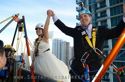 "Bride Rebecca Shackelford and groom Carlos Gato, rappel down the JW Marriot Marquis moments of exchanging vows on the 19th floor on Sept. 5, 2013. The couple won the opportunity to be ""Wed Over The Edge"" by the Miami Children's Initiative,  which held the fundraising event ""Over The Edge"" on Sept. 5, 2013 to raise money for children in Liberty City."