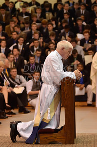 Mike Vogt kneels before Bishop Malooly with the entire Salesianum School student body and faculty watching during his Ordination in the Gym of Salesianum School, Wilmington, Del., Friday, January 27, 2012. Mike Vogt ask Bishop Malooly for permission to have his Ordination in the gym of Salesianum School where he is a teacher. photo/Don Blake Photography.com