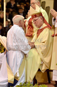 Mike Vogt kneels before Bishop Malooly as he places his hand in those of the Bishop as a sign of fidelity during his Ordination in the Gym of Salesianum School, Wilmington, Del., Friday, January 27, 2012. Mike Vogt ask Bishop Malooly for permission to have his Ordination in the gym of Salesianum School where he is a teacher. photo/Don Blake Photography.com