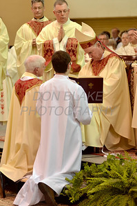 Mike Vogt kneels before Bishop Malooly as his palms are anointed with Sacred Chrism during his Ordination in the Gym of Salesianum School, Wilmington, Del., Friday, January 27, 2012. Mike Vogt ask Bishop Malooly for permission to have his Ordination in the gym of Salesianum School where he is a teacher. photo/Don Blake Photography.com